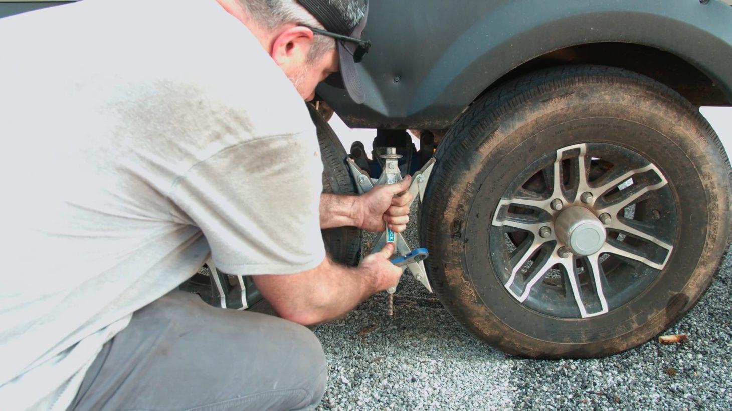Person using tire chocks to change a flat tire