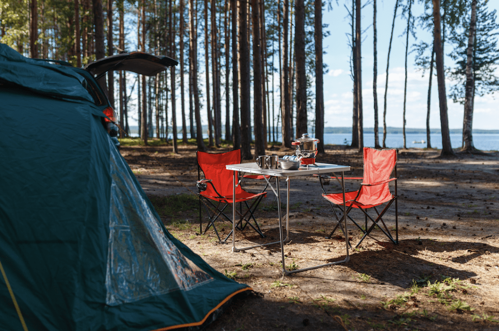 Folding table and two red camping chairs next to a pitched tent among tall trees with a lake view in the background