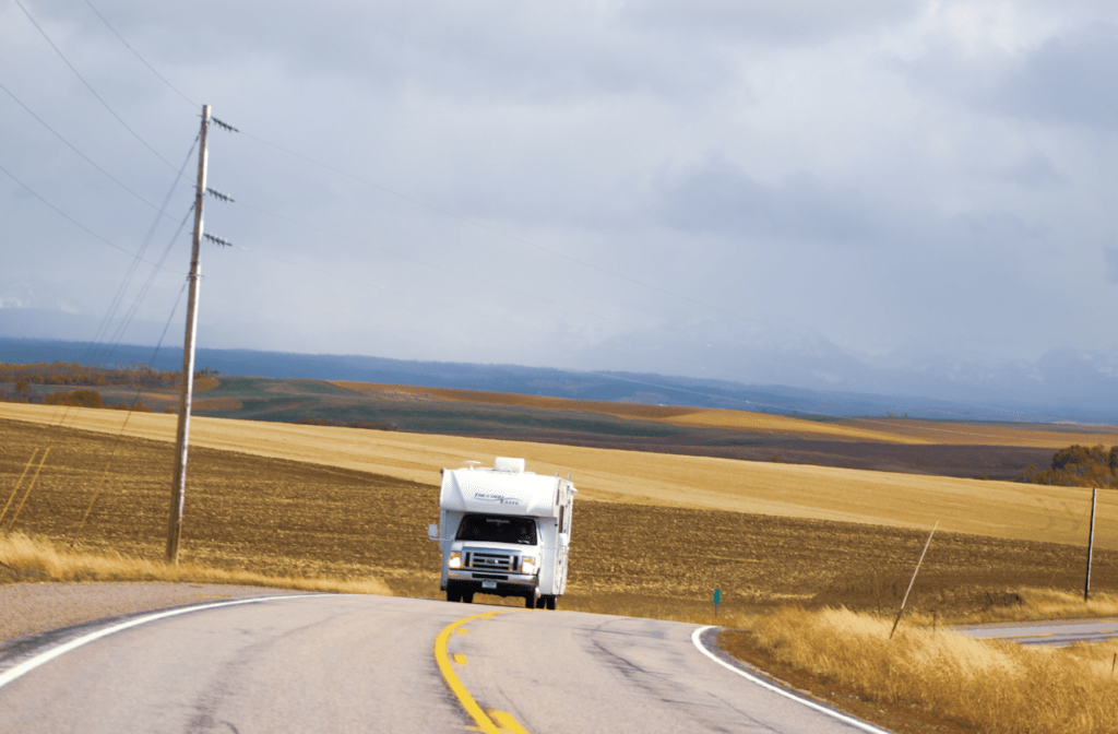 Class c motorhome driving on two lane road surrounded by golden rolling hills and grasses with cloudy mountains in the distance