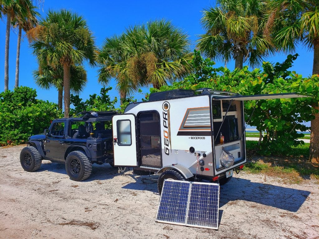 Jeep pulling a small trailer at the beach with portable solar panels resting on the ground