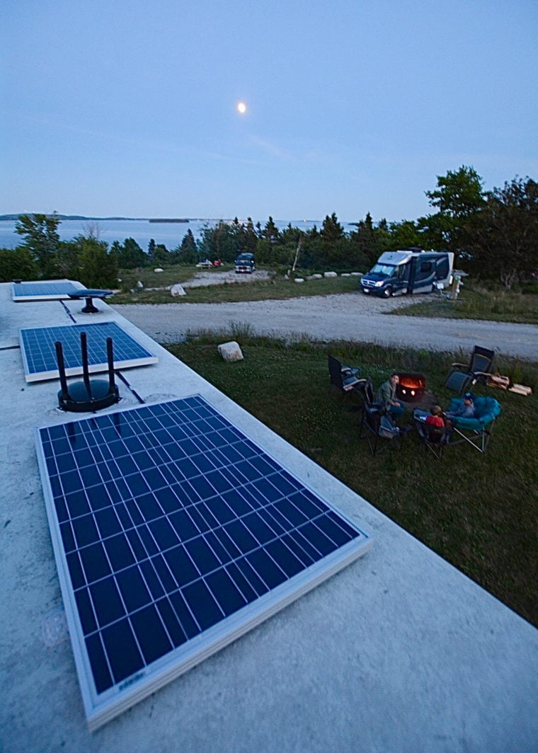 Evening photo of solar panels on top of an RV at a campground