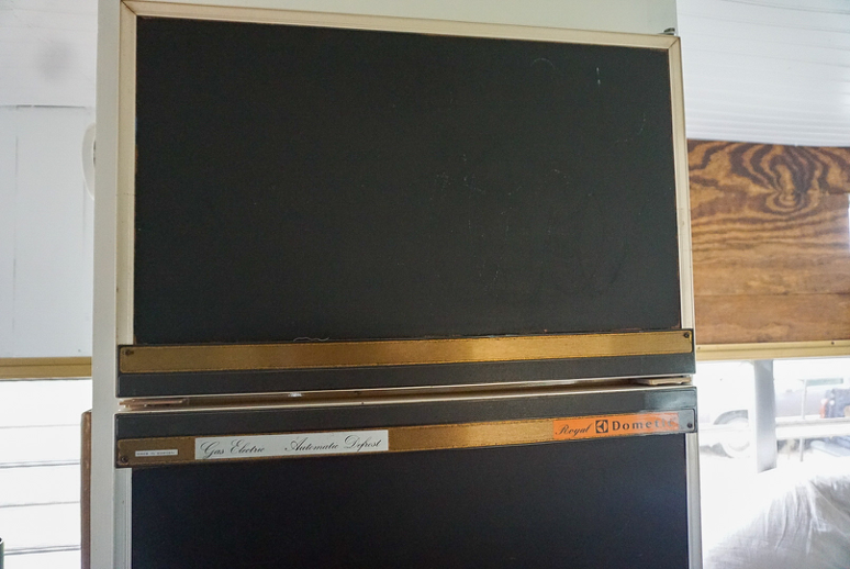 Close up of old RV fridge with black chalkboard paint on front