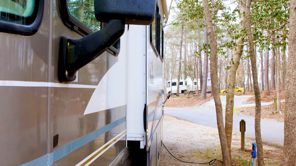 Close up of the side of a Class A motorhome plugged into hookup pole, next to trees