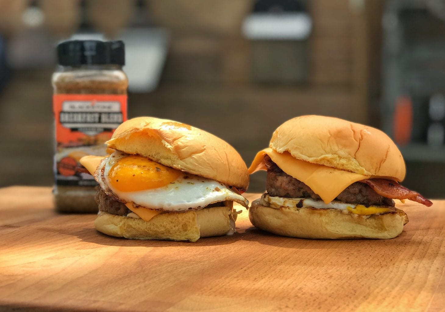 Two breakfast sandwiches on wooden table