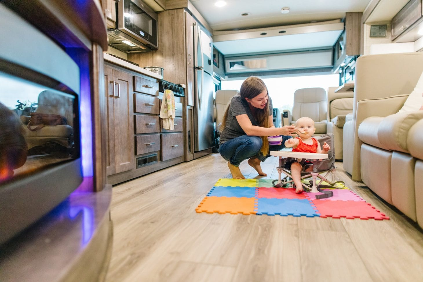 baby being fed on floor of rv
