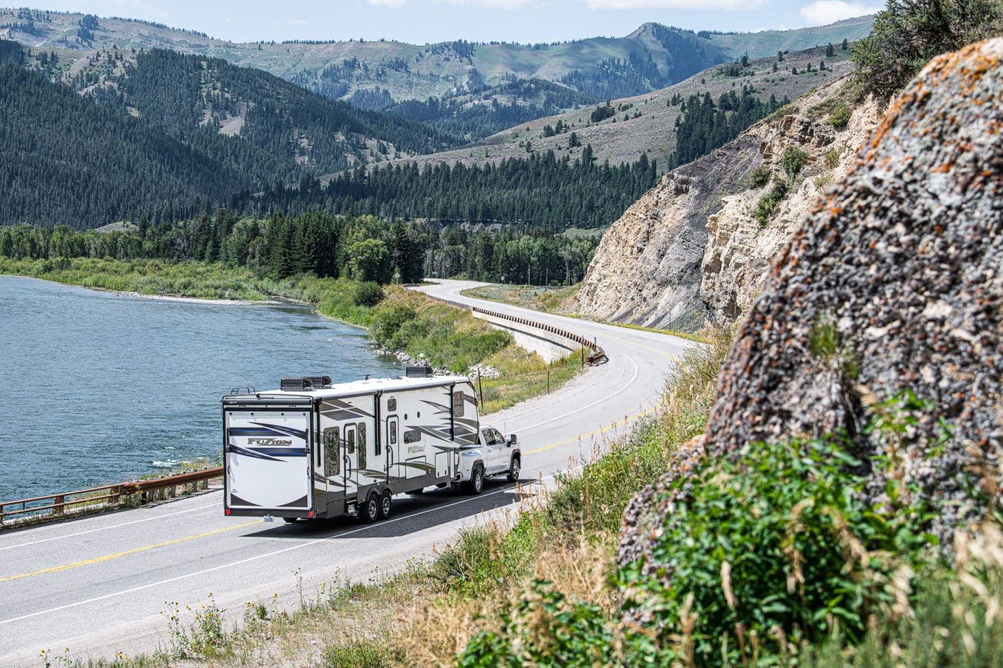 Toy hauler travel trailer being towed by a pickup truck through winding road