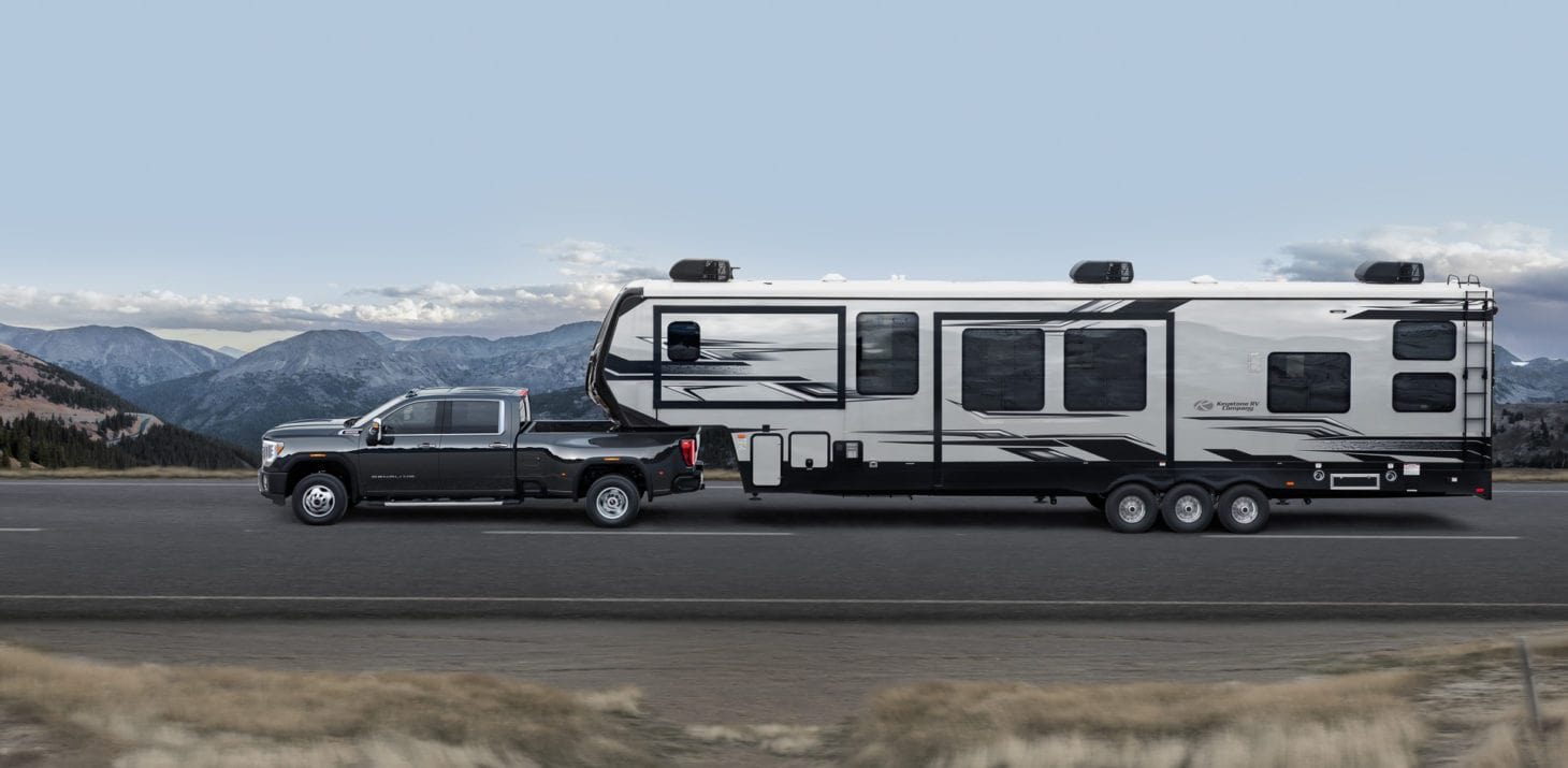 Truck towing fifth wheel travel trailer through mountains