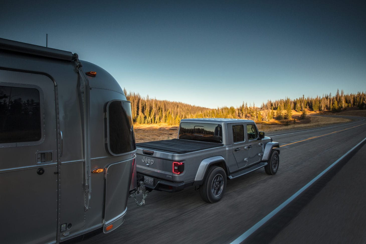 Truck towing an Airstream travel trailer on road