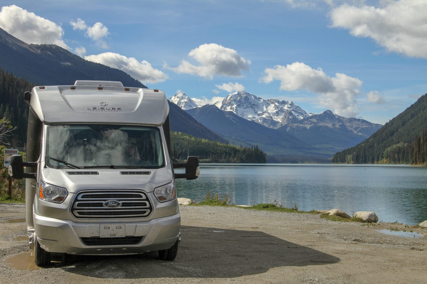Motorhome parked next to lake with mountain backdrop