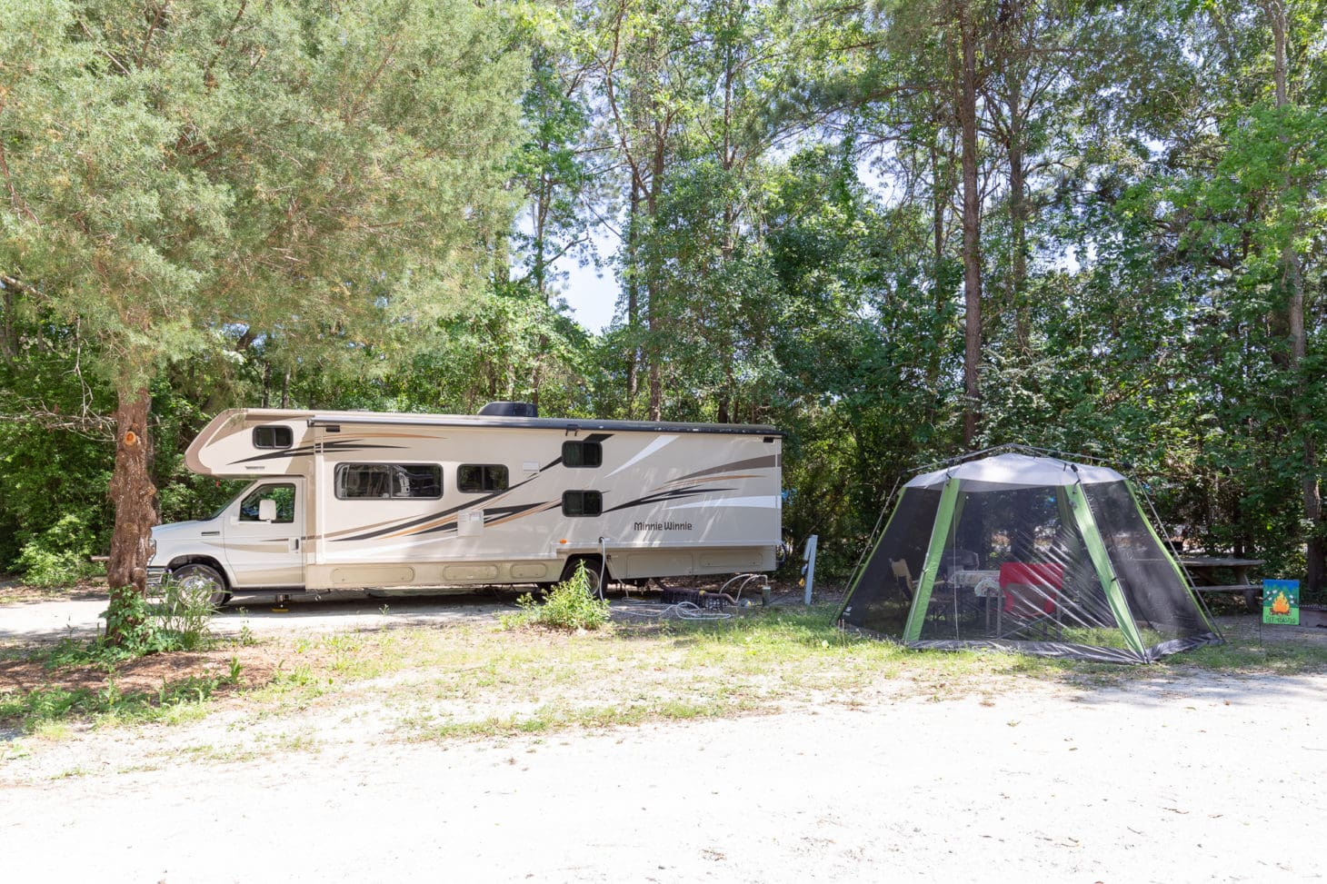 Motorhome parked at campsite with tent set up in wooded area
