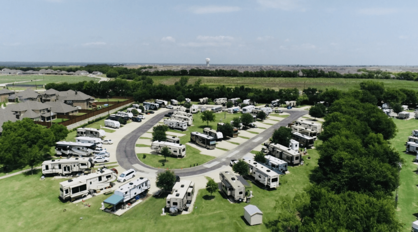 RV parking lot with clubhouse and city in the distance