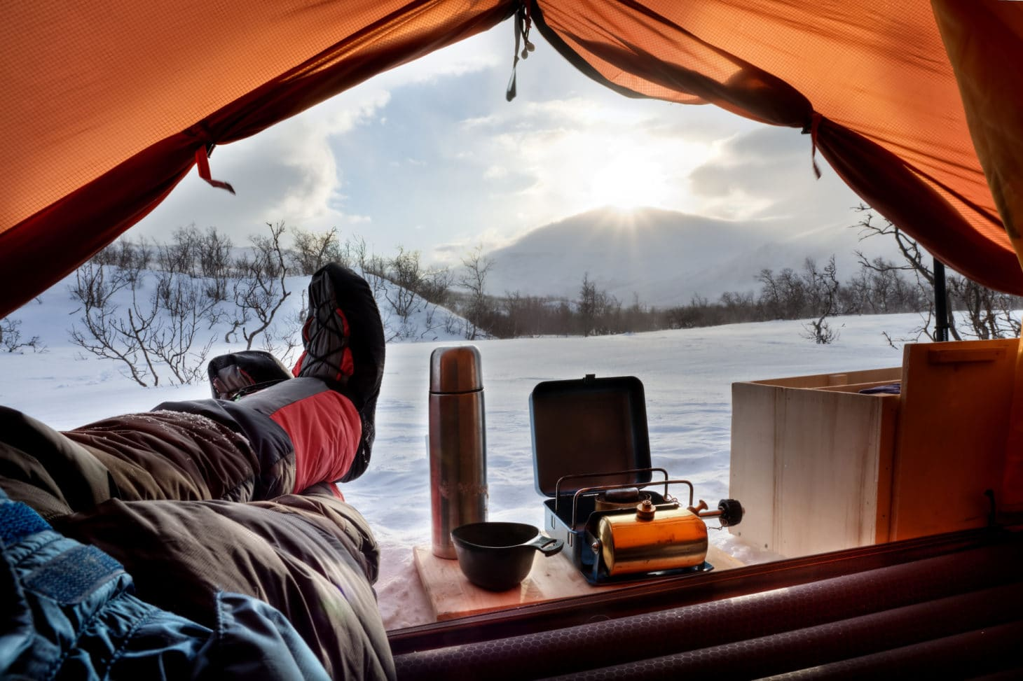 Open tent during a winter morning with camp cooking gear