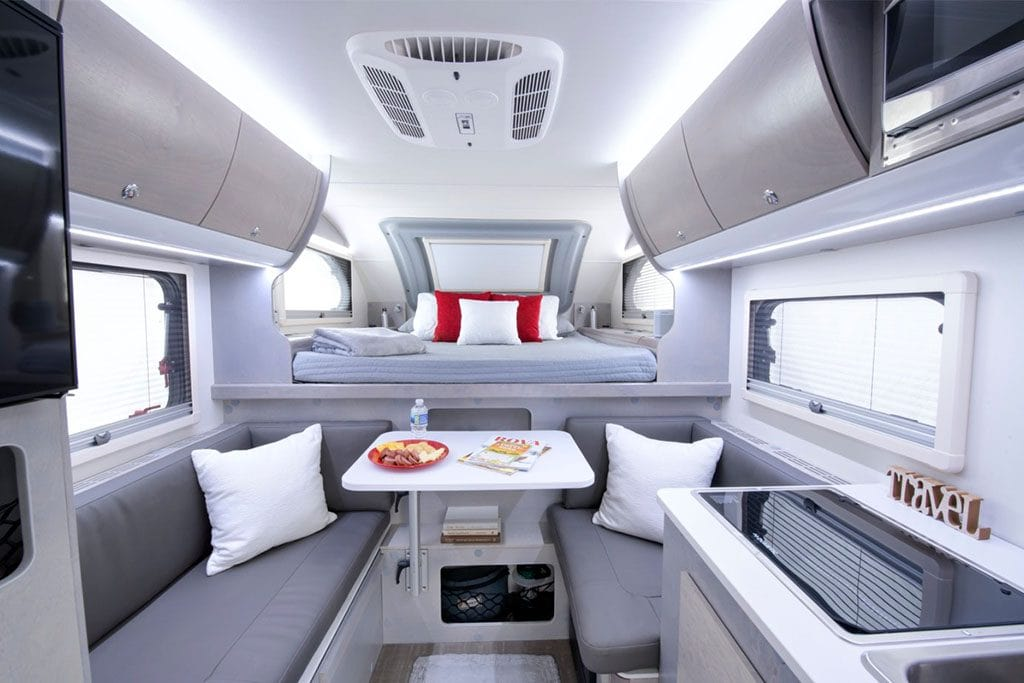 Interior view of truck camper with platform bed and seating area.