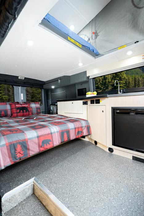 View of transformed dinette to bed in the rear of a Class B van with view of pop-up bed