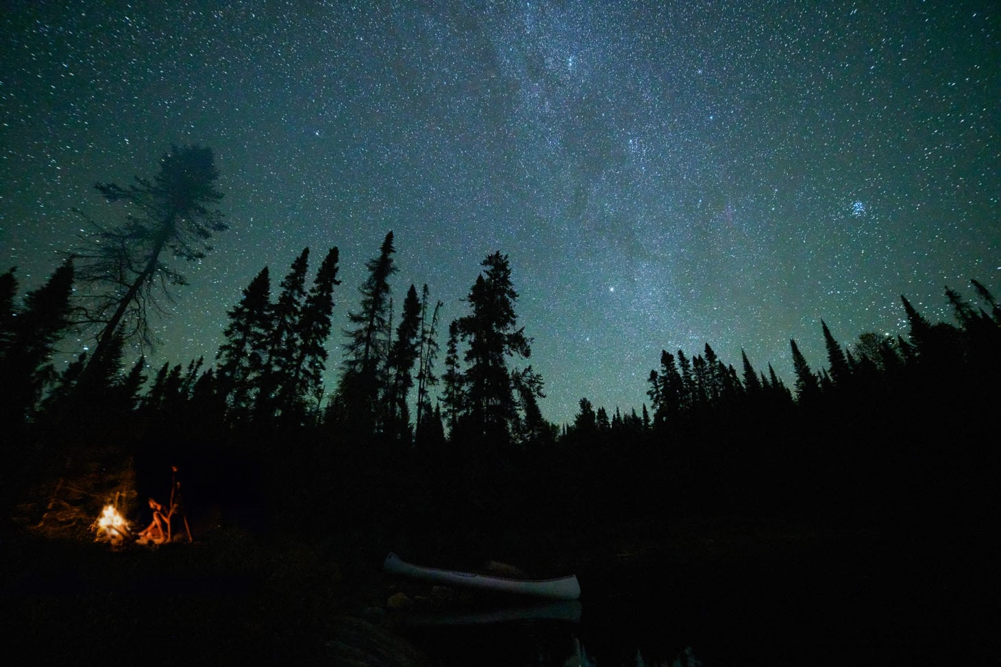 Wide angle view of starry night ski with campers sitting around fire