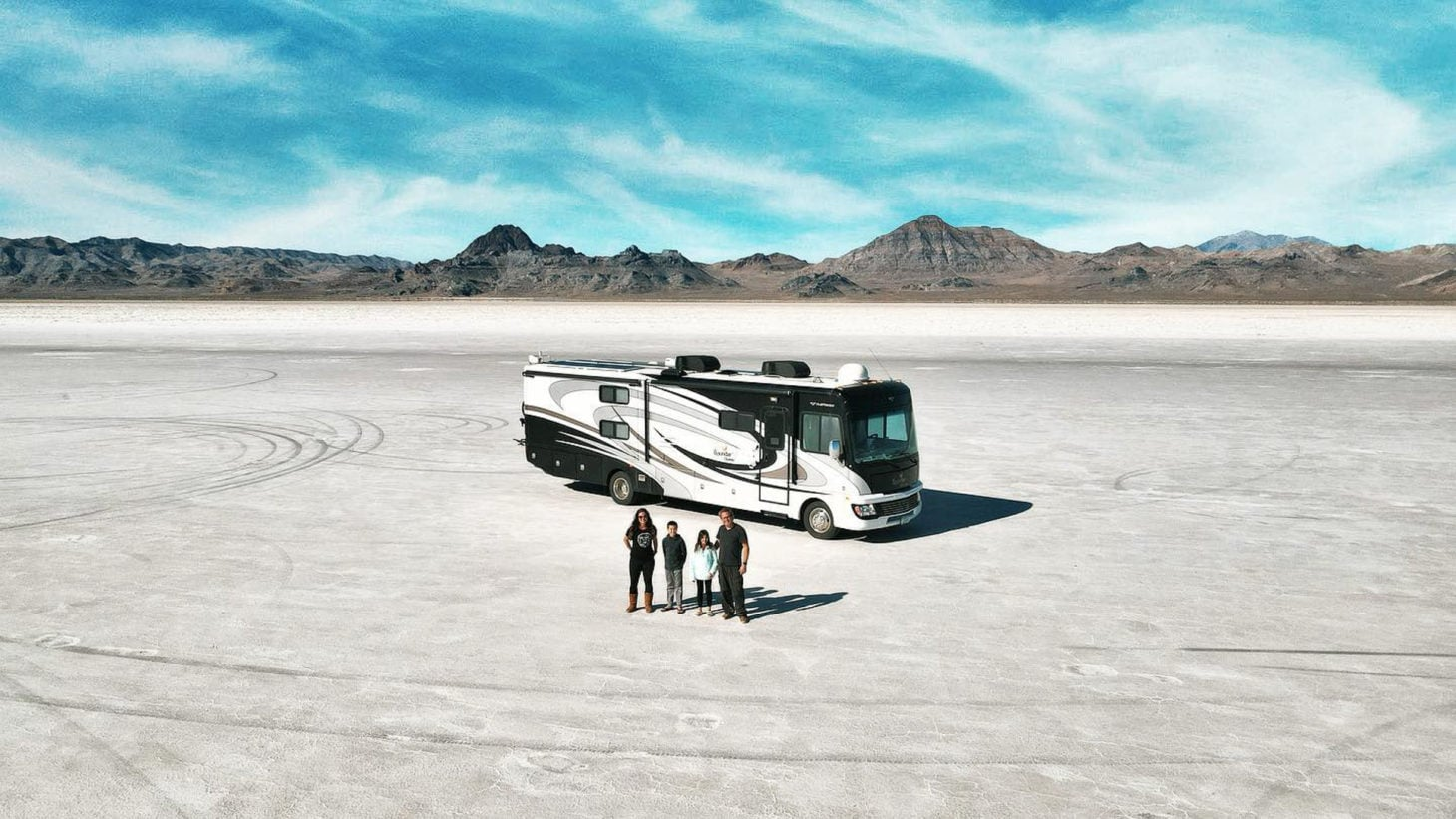 Aerial view of RV parked on salt flats with family posing in front