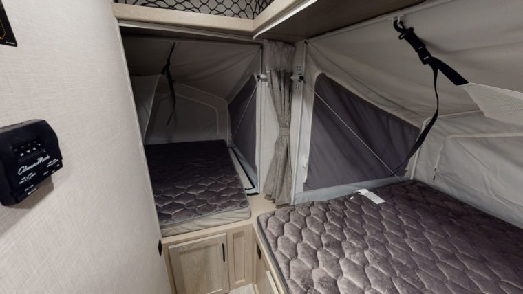 Sleeping area of an RV trailer with two queen-sized beds