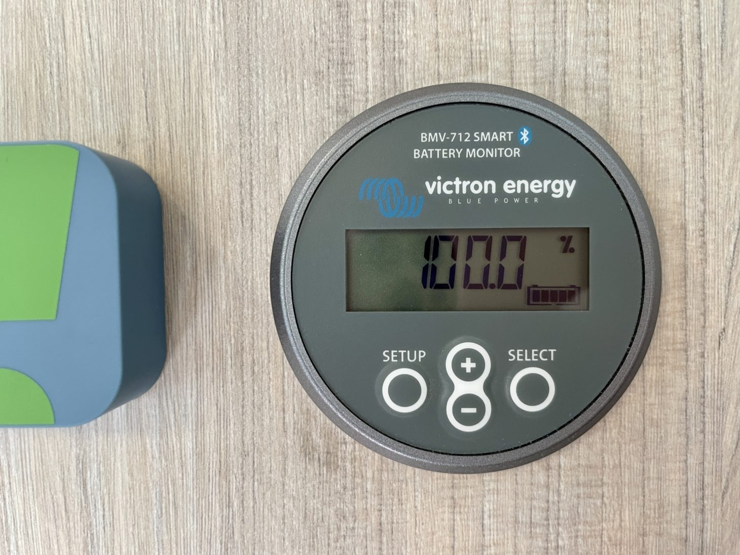 View of RV battery monitor wall-mounted display showing fully charged battery