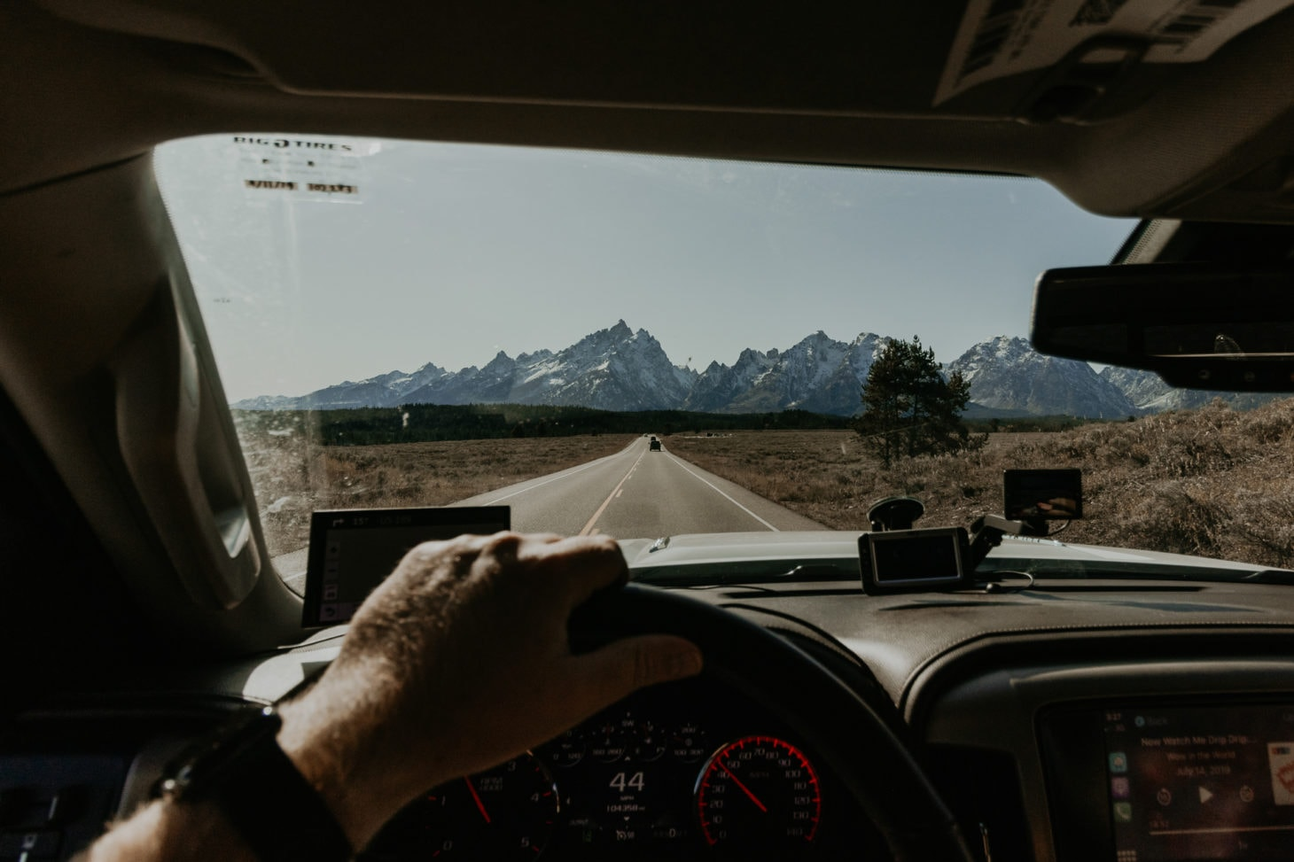 View from the dashboard of a car heading to mountain range