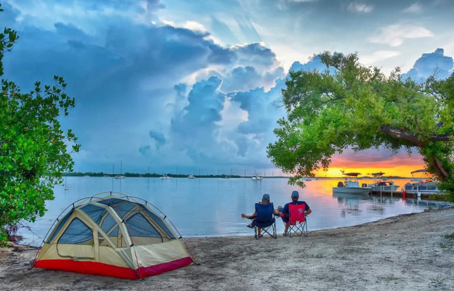 Couple sitting on beach chairs on shoreline with tent and boats parked at nearby dock