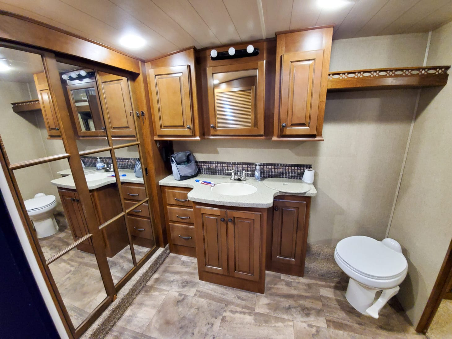 Interior of a large RV bathroom with lots of cabinet storage, sink, toilet, mirror, and shelving