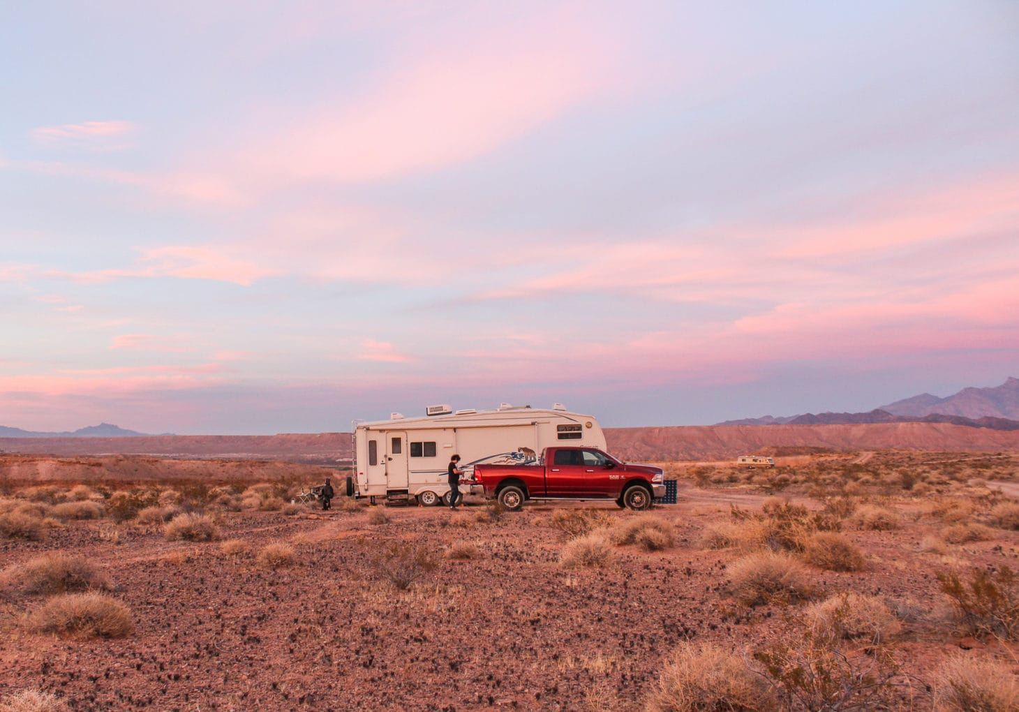 A pickup truck is parked next to a fifth wheel RV as sun sets. There is one other RV in the background